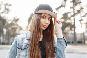 Young hipster girl in a baseball cap on a sunny day